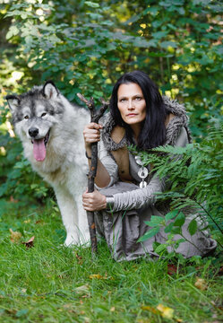 Forest dweller woman with a large dog Alaskan Malamute