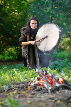 Shaman woman drumming next to the fire in the evening forest
