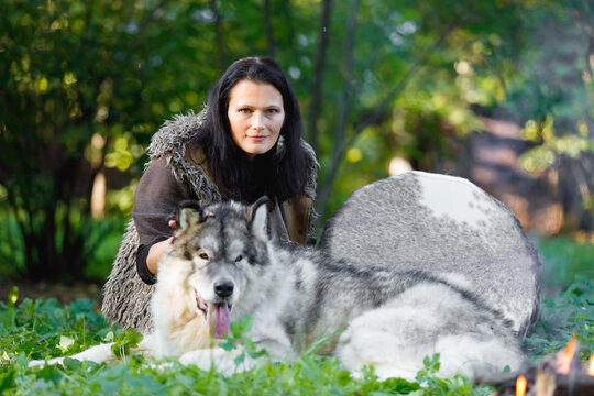 Shaman woman with an Alaskan Malamute dog next to the fire in the forest