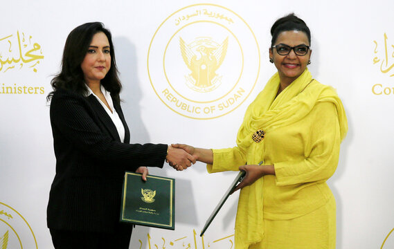 Acting Minister of Finance and Economic Planning, Heba Mohammed Ali shakes hands with Mai Abdelhalim of General Electric Co.