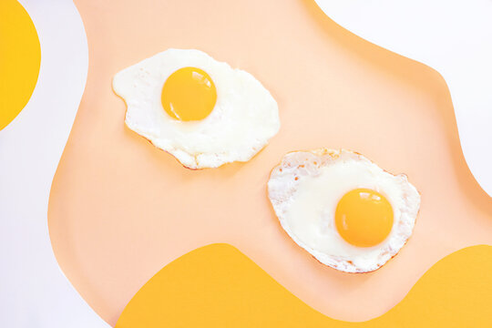 Fried eggs on a light white and yellow wavy background. Paper art. Breakfast concept, fried food.