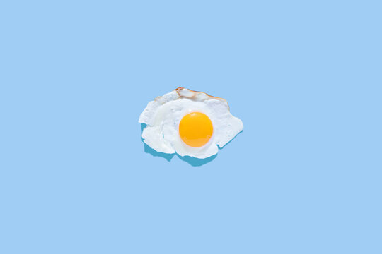 Fried eggs on a light blue background. Minimalism, top view. Breakfast concept, fried food.