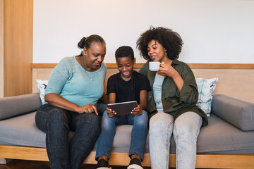 Grandmother, mother and son using digital tablet.
