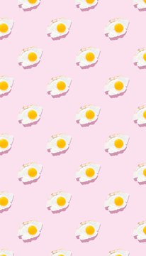 Fried eggs on a light pink background, pattern. Minimalism, top view. Breakfast concept, fried food.