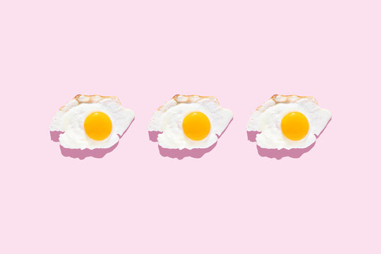 Fried eggs on a light pink background. Minimalism, top view. Breakfast concept, fried food.