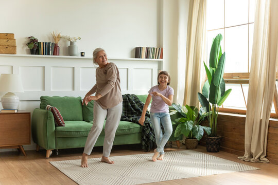 Joyful granny middle aged elderly woman dancing to energetic music with little granddaughter. Happy smiling two generations female family having fun together in living room.