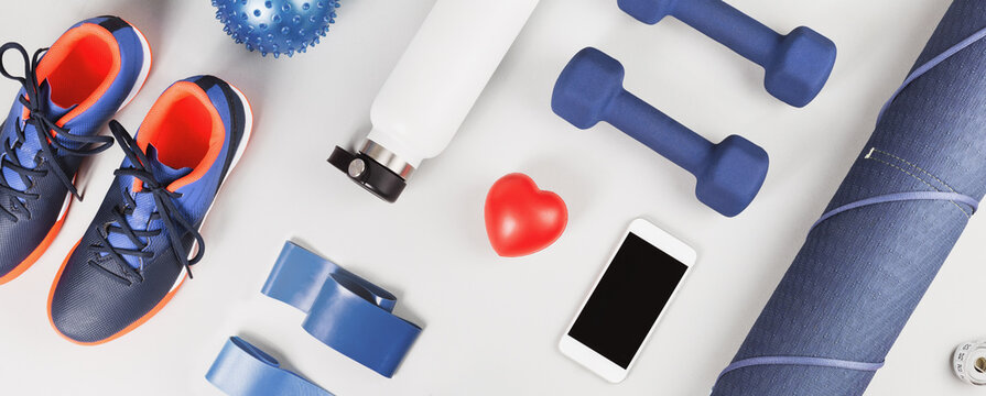 Sports banner. Healthy lifestyle blue and red gender neutral sports accessories knolling flat lay with heart and smartphone in the middle. Fitness yoga and exercise and weight management concept