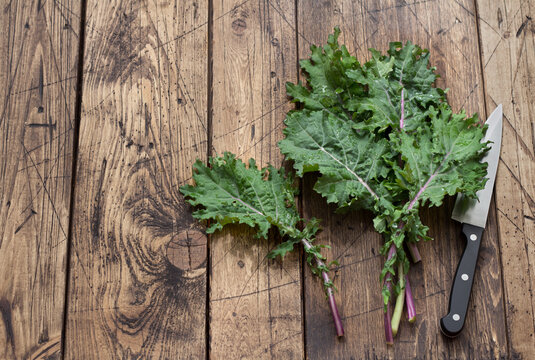 Fresh kale leaves on the wooden background. top view. space. rustic style. healthy food. superfood