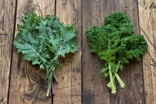 Fresh variety kale leaves on the wooden background. healthy food. superfood. flat lay. rustic style.