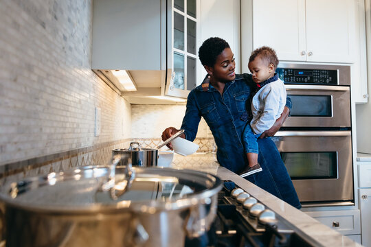 Black mother and son in kitchen preparing food for family dinner