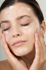 Beautiful young girl cleansing face with cosmetic facial skincare foam, gel or soap.