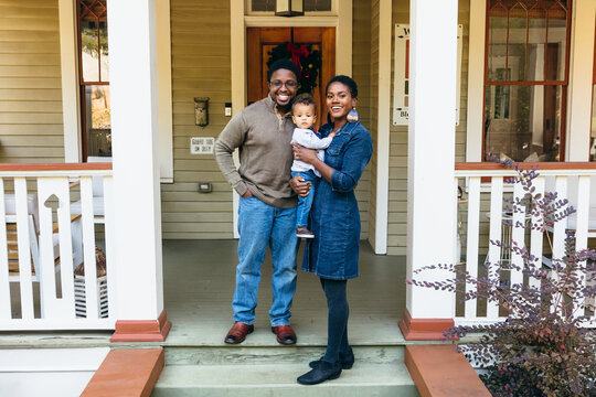Potrait of black family and child in front of home for the holidays