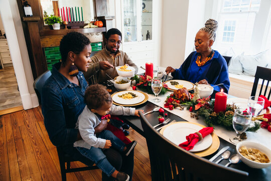 Black multigenerational family eating Kwanzaa holiday meal