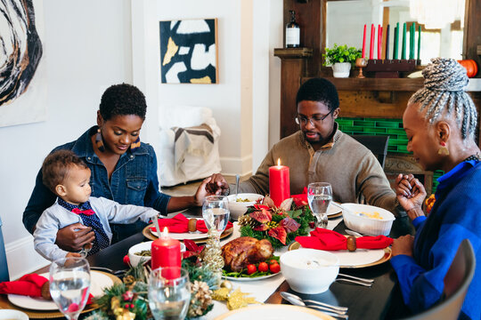 Black multigenerational family praying and blessing the food for Kwanzaa holiday meal