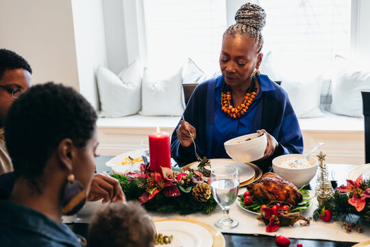 Black multigenerational family and senior woman eating holiday meal