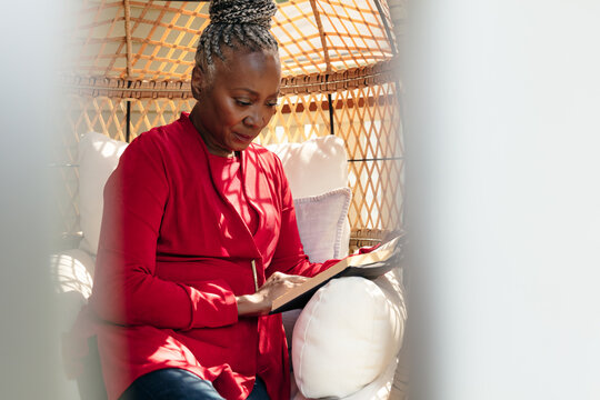Senior Black woman with grey hair sitting outside and reading book