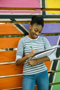 Young Black teen girl drawing in notebook at school