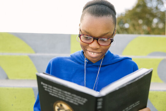 Black female teenager with glasses studying for school outside