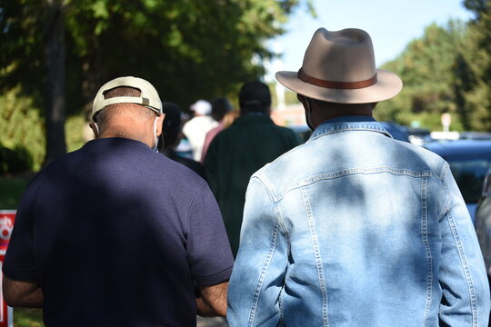 2 African American men stand in line for the first day of early voting in North Carolina.