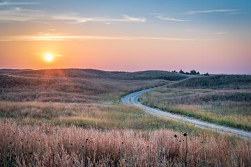 hazy sunrise over Nebraska Sandhills with a dirt sandy road at Nebraska National Forest, fall scenery affected by wildfire smoke from Colorado and Wyoming