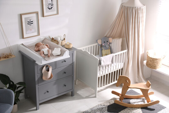 Cute little baby on changing table in room