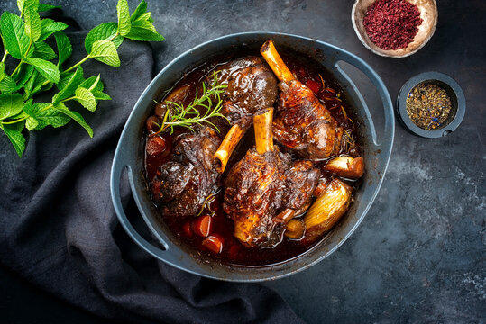 Modern style traditional braised slow cooked lamb shank in red wine sauce with shallots and carrots offered as top view in a design stewpot