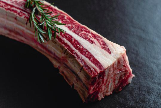 Short Rib asado de tira de res vaca carne roja en fondo negro con romero