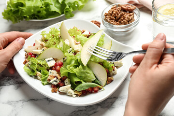 Woman with tasty pear salad at white marble table, closeup