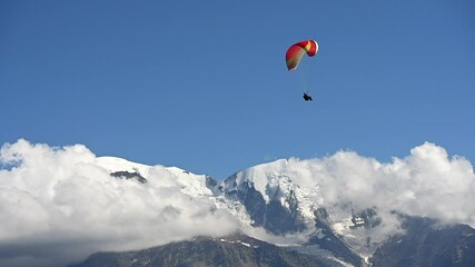 Wall Mural - Paraglider Above Snowy Mountain Peaks Enjoying His Flight in Slow Motion Movement.
