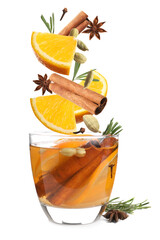 Cut orange and different spices falling into glass of mulled wine on white background