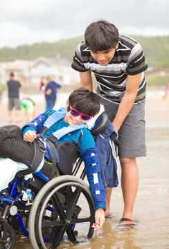 Young man pushing disabled little boy in wheelchair on beach