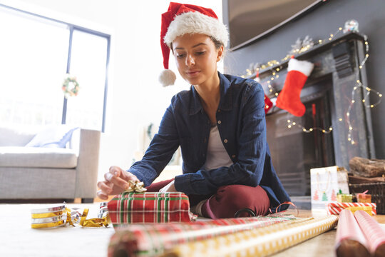Woman in Santa hat wrapping Christmas presents at home