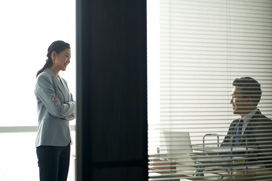 asian businessman and businesswoman chatting in office