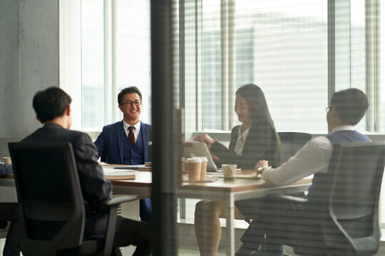 team of asian corporate executives discussing business in conference room