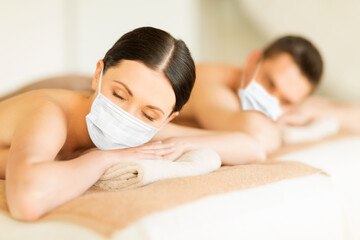 wellness, bodycare and health concept - couple wearing face protective medical masks for protection from virus disease at spa