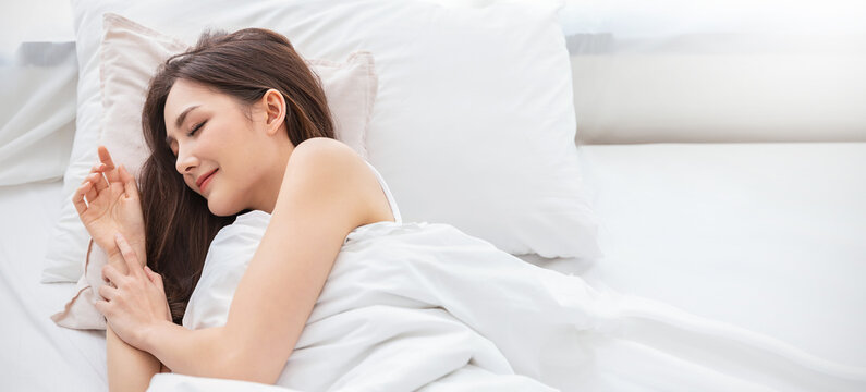 Portrait of beautiful young asian woman smile enjoy fresh soft bedding linen and mattress in bed room modern apartment. Teenage asia girl resting, good night sleep concept panoramic banner