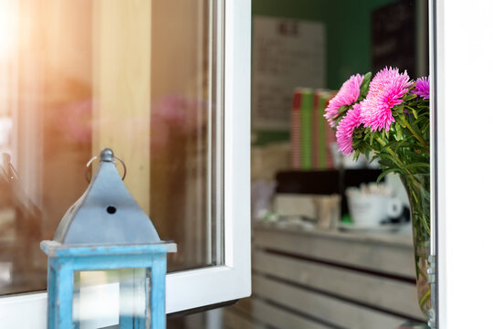 Open window with pink daisy flowers in vase of street city urban cafe with tee or coffee to go and warm sunrise sun reflection in glass. Welcome hospitality concept. Interior fresh plant decoration