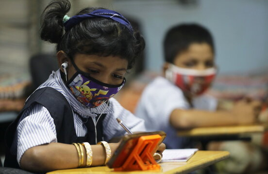 A student wearing a protective mask writes notes from an online lecture on a mobile phone, inside a digital mobile education library, initiated to provide mobile phones to chidren who have no access to them for their education classes  in Mumbai