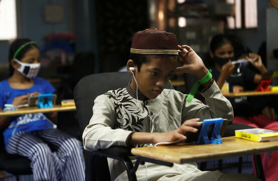 Children watch online lectures on mobile phones, inside a digital mobile education library, initiated to provide mobile phones to chidren who have no access to them for their education classes in Mumbai