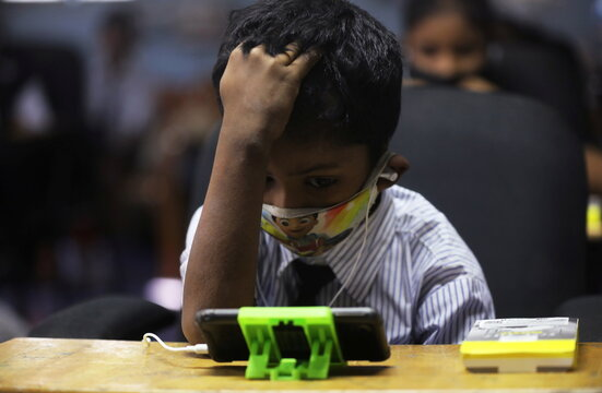 A student watches an online lecture on a mobile phone, inside a digital mobile education library, initiated to provide mobile phones to chidren who have no access to them for their education classes in Mumbai