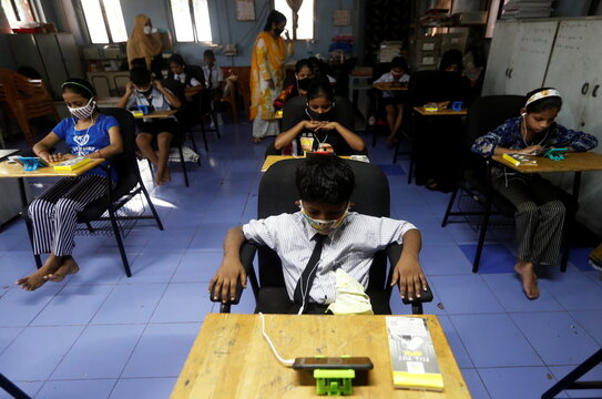 Students watch online lectures on mobile phones, inside a digital mobile education library, initiated to provide mobile phones to chidren who have no access to them for their education classes in Mumbai