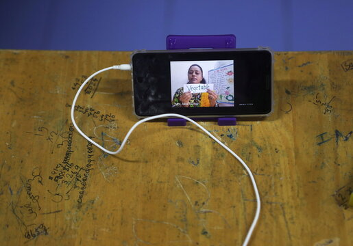 A teacher is seen on a mobile phone during an online lecture, inside a digital mobile education library, initiated to provide mobile phones to chidren who have no access to them for their education classes in Mumbai