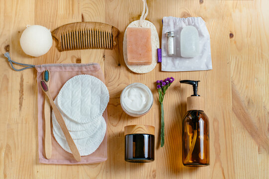 Zero waste bathroom accessories, wooden comb, deodorant, shea butter, solid soap and shampoo bars, reusable cotton make up removal pads, make up remover in a glass container.