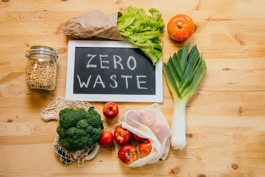 Zero waste lifestyle, top view on wooden table background with broccoli, salad, leek, apples, pumpkin, glass bottle with soy, black board with text Zero Waste, eco friendly green vegetables.