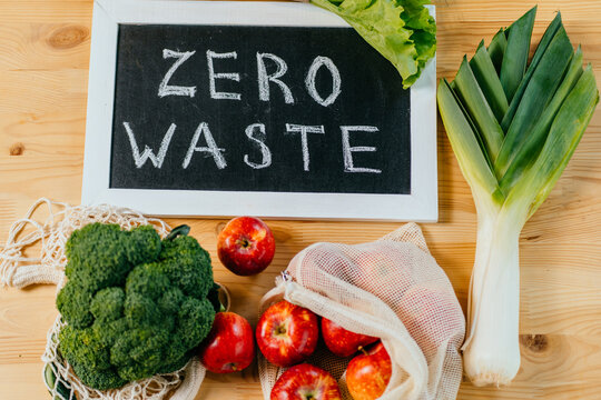 Zero waste lifestyle, flat lay, top view on wooden table background with broccoli, salad, leek, apples, pumpkin, black board with Zero Waste text, eco friendly green vegetables. Vegan, minimalism.