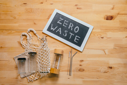 Zero waste lifestyle, set for shopping, top view on wooden table background with smartphone, glass bottles, net bag, black board with text Zero Waste, vegan, minimalism, healthy food concept