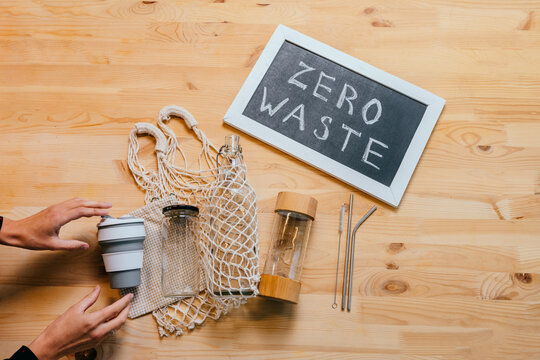 Zero waste lifestyle, set for shopping, top view on wooden table background with smartphone, glass bottles, cup, net bag, black board with text Zero Waste, vegan, minimalism, healthy food concept