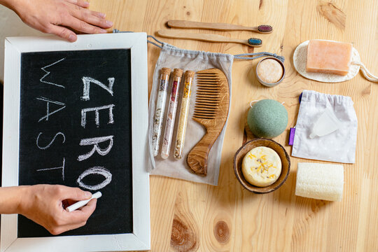 Woman's hands writing Zero waste on tablet sign on counterbar. Eco-friendly bathroom accessories, reusable sponges for washing, tooth powder, toothbrushes, washcloths, loofah, wooden hair comb.