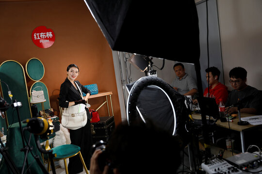 Sun Shaqi displays handbag during a livestreaming session for the second-hand luxury goods retail platform Plum in Beijing