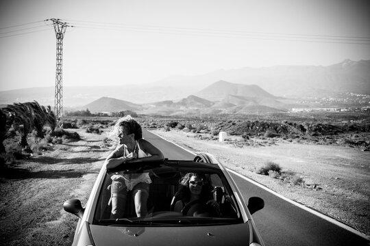 Black and white conceptual travel and adventure with friends concept with couple of young middle age women traveling on a convertible car in a long road sith mountains in background - freedom life
